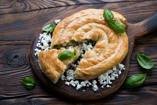 Burek stuffed with cheese and spinach in a rustic wooden setting