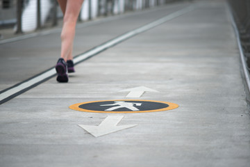 Label on pavement designating a pedestrian walking path, women's legs jogging past.