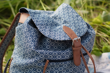 Girl's backpack with a blue pattern and a brown leather strap