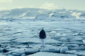 Woman standing on ice floe on frozen lake, Iceland
