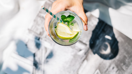 Overhead view of hand holding glass of water with fresh lemon, lime, mint and ice-cubes
