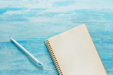 Single simple empty white notebook with a blank for drawing or writing and white plastic pen are on a Desktop from blue wooden plank. Top view. Mockup. Flat lay