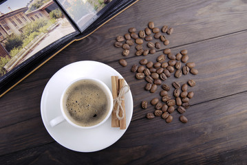Coffee cup, beans and cinnamon on wood background