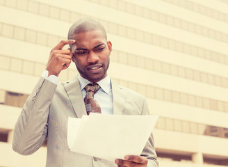 Confused executive man looking at documents outside corporate office building