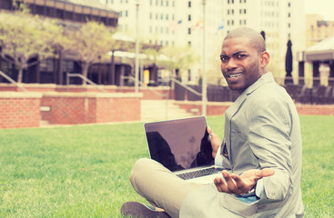 Frustrated angry business man with laptop sitting outdoors corporate office