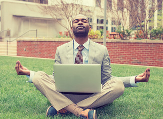Young businessman with laptop meditating in lotus pose taking a deep breath