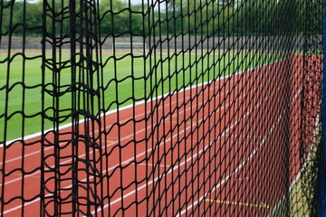 Safety net at a athletic stadium, running tracks and football pitch as a background
