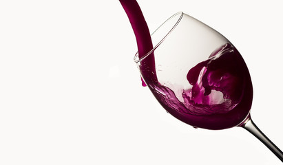 Red wine pouring in a wineglass on white