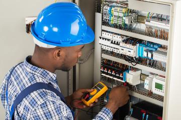 Technician Examining Fusebox With Multimeter Probe
