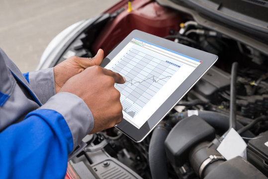 Mechanic With Digital Tablet While Examining Car