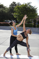Yoga instructor and student in the park