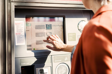 Midsection of businesswoman using ticket machine at railroad station