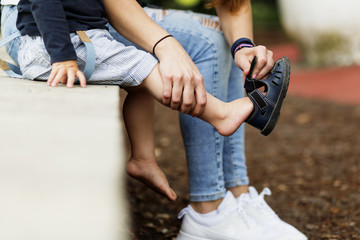 Cropped image of mother assisting son in wearing sandal at park