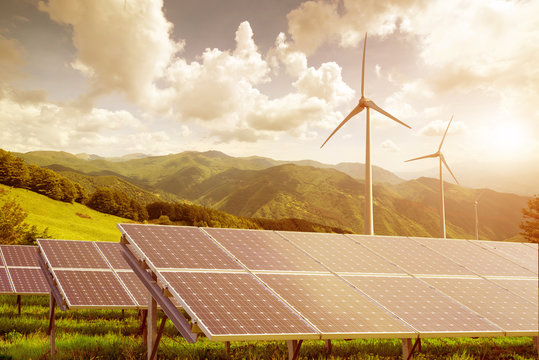solar panels and wind turbines against mountanis landscape again
