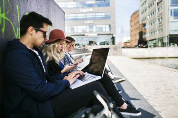 Side view of freelancers using laptops in city