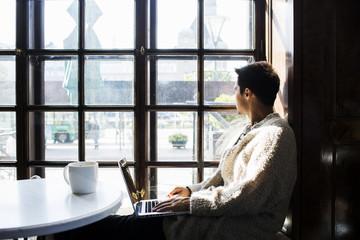 Freelancer looking through window while using laptop at cafe