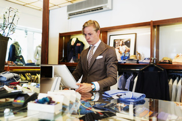 Handsome owner working on computer at checkout counter in clothing store