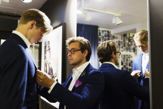 Tailor fitting man's suit