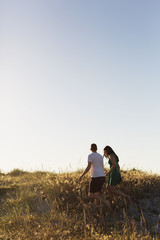 Couple walking on grassy field against clear sky