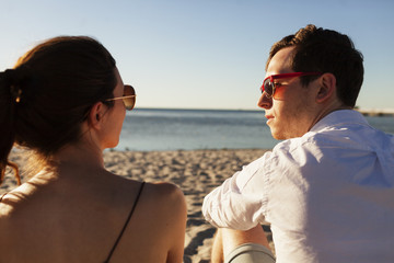Rear view of young couple sitting on beach