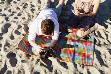 Man using digital tablet and friend writing on book at picnic