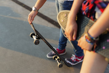 Midsection of teenage girls with skateboards at skate park