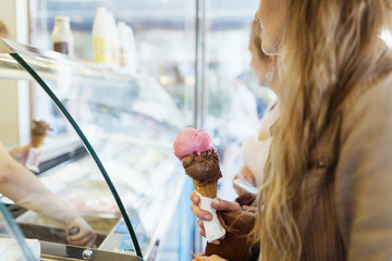 Midsection of woman holding ice cream cone at parlor