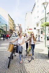 Women with bicycles and shopping bags walking on cobblestone street