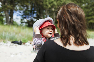 Rear view of mother holding baby boy at beach