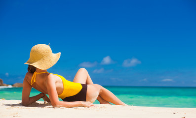 Fit woman in sun hat and bikini at beach.remote tropical beaches and countries. travel concept