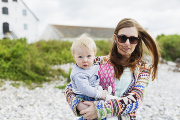 Mother in sunglasses holding son on grassy field