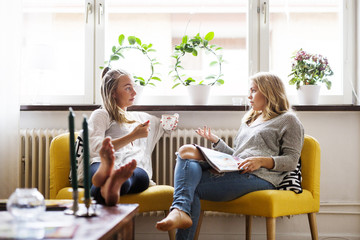 Young woman discussing with female friend holding coffee in living room