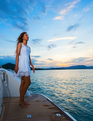 Young beautiful woman in white dress  standing on the yacht in sunset time.