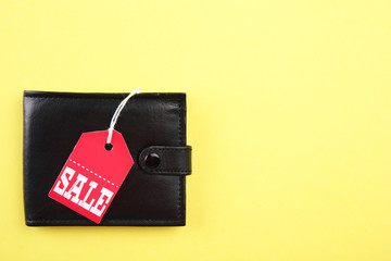 Wallet with sale tag on yellow background