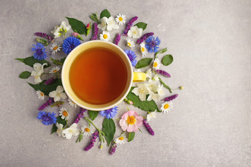 Cup of tea with fresh flowers lying around on color background