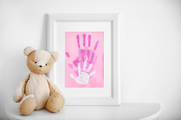 Family hand prints in frame on table
