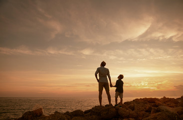 Father with son on the sea coast in sunset time