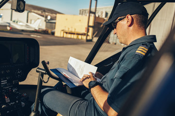 Helicopter pilot reading a manual book
