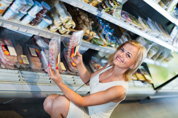 Woman choosing meat in refrigerated section in food store