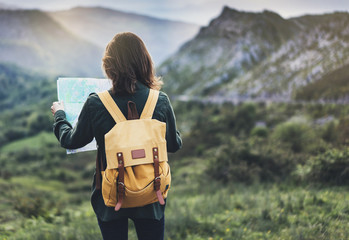 Hipster young girl with bright backpack enjoying sunset on peak mountain, looking a map. Tourist traveler on background valley landscape view mockup, sunlight in trip in northern spain basque country
