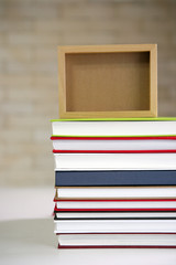stack of books with wooden photo frame