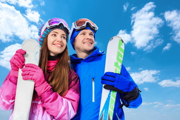 Smiling couple with skis