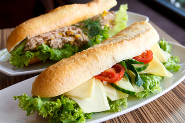 Cheese and salad baguette on white plate. Tuna baguette in backg