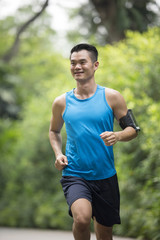 Sporty Asian man running outdoors. Action and healthy lifestyle