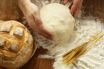 Chef hands with dough and homemade natural organic bread and flour on a wooden background