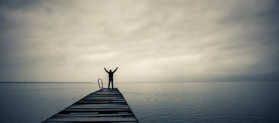 Fototapeta Man standing on a old wooden dock with raised hands obraz