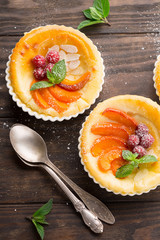 Homemade Tartlets with cottage cheese and fresh fruits on rustic wooden background, top view