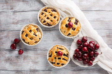 Homemade Cherry mini pies with fresh berries, top view