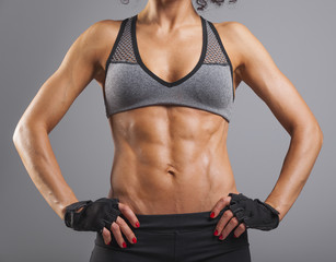 Muscular woman standing on grey background