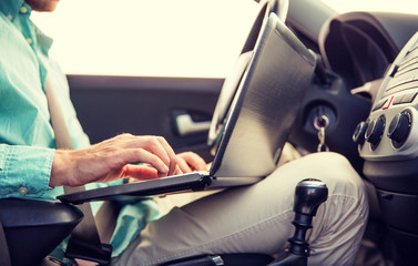 close up of young man with laptop driving car